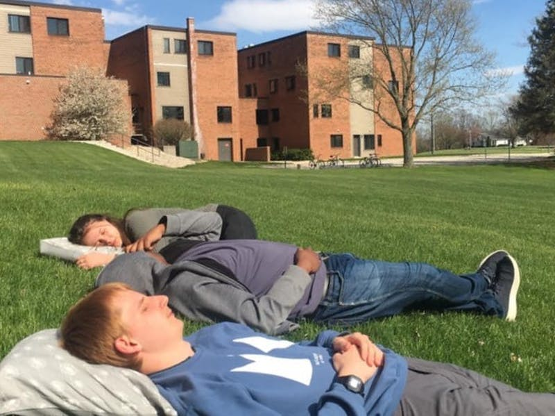From front, students Daniel Robb, Jason John and Autumn Thompson take a break from their studies for a socially distanced rest in the sun outside Gerig Hall.