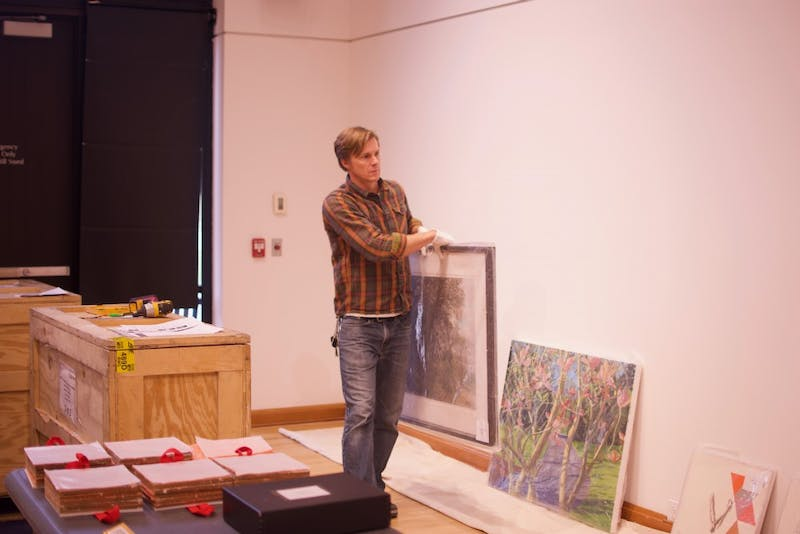 Gallery curator Jeremie Riggleman sets up the new exhibit.