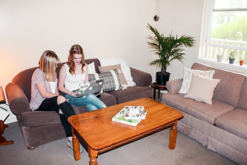 Seniors Sophie Finlay and Sara Bergen enjoy the serenity of their cozy apartment while doing homework.