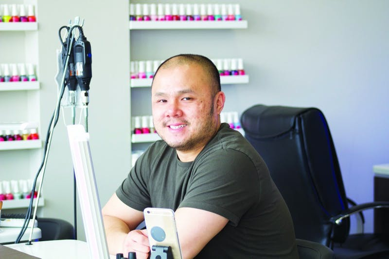 Polished owner Danny Dang sits at one of two nail counters at his store. Not pictured are the pedicure stations and multitude of nail polish colors. (Photograph provided by Katherine Upton)