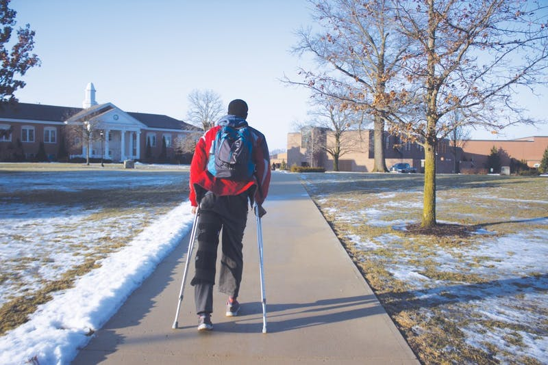 Senior Emmanuel Boateng navigates campus on crutches.