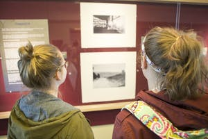 GVL / Sara Carte - Grand Valley students, (left to right) Alison Farnsworth and Brittany Patrosso, look at the Flashladder Gallery Exhibit in Lake Ontario hall on Friday, March 18, 2016.