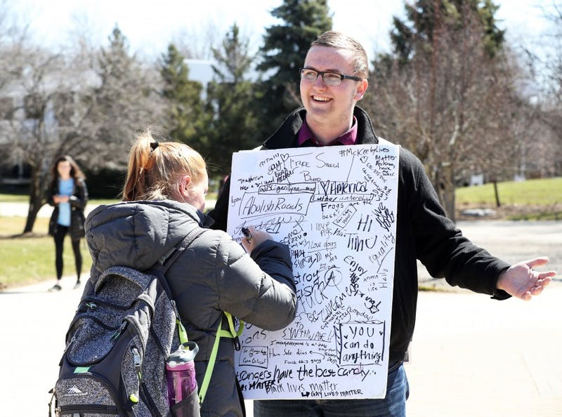GVL/Kevin Sielaff - A Grand Valley student writes on Nathan Williamson's free speech board on Wednesday, Mar. 22, 2017 outside of Zumberge Hall on Grand Valley's Allendale campus.