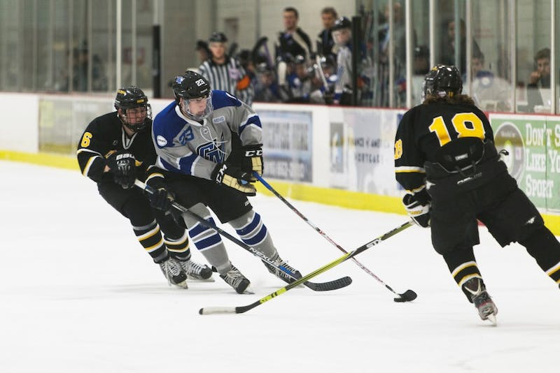 GVL/Luke Holmes - Scott Schueneman (23) tries to protect the puck from the surrounding defenders. Grand Valley D3 Men's Hockey had a victory over Adrian College Saturday, Jan. 30, 2016.