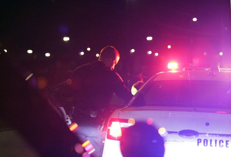 Officer Seth Beelen places an individual in the police car on Saturday October 28, 2017. GVL / Archive