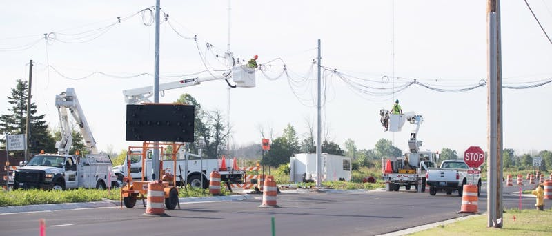GVL/Kevin Sielaff - Strain Electric crews install overhead wiring at the intersection of West Campus Drive and 48th Ave. Thursday, August 18, 2016.