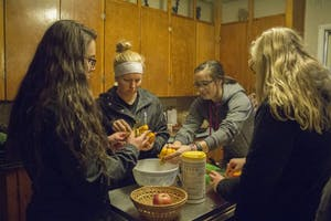 GVL/Mackenzie Bush - Emily Smith (left), Lexi Henckel (middle), Skylar Swifink (right) and Maddie Buning (far right) cut and prepare winter squash at the Sustainable Agriculture Project Monday, Oct. 24, 2016 during the Fresh From the Garden event.