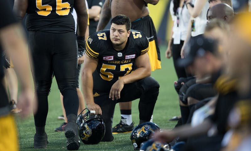 GVL/Kevin Sielaff - Brandon Revenberg (57) rests on the sideline in between plays. The Hamilton Tiger-Cats square off against the Saskatchewan Roughriders Saturday, August 20, 2016 in Hamilton, Ontario.