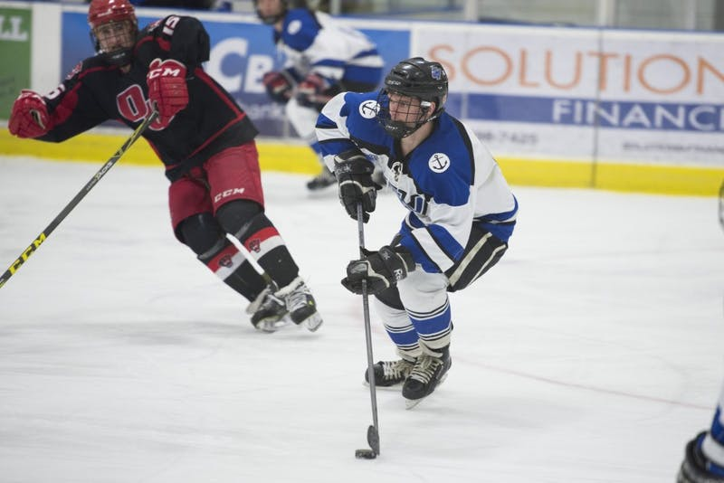 GVL / Luke Holmes - Tom Lusynski (4) skates by his defender with the puck. The Grand Valley D2 hockey team won 5-2 over Davenport University at Georgetown Ice Arena Saturday, Feb. 20, 2016.