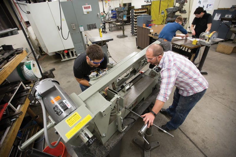 GVL / Kevin Sielaff – Members of Grand Valley's Formula SAE Racing Team (Chris Clark, right; Bert Vossler, left) work on marchining push-rod plugs for the vehicle's suspension inside of the Eberhard Center's engineering labs Thursday, March 17, 2016.