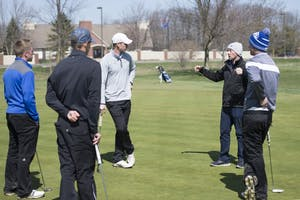 GVL / Luke Holmes - Head Coach, Gary Bissell talks to the team on the practice green at The Meadows Golf Course Tuesday, Apr. 5, 2016.
