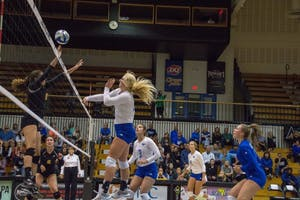 Staci Brower spiking the ball towards Michigan Techs blockers, Friday, Sept. 29, 2017. GVL / Dylan McIntyre.