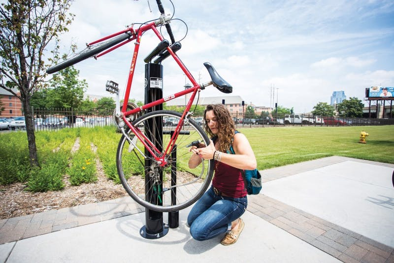 GVL / ArchiveGVSU student, Annie Taccolini, uses one of the new bike repair stations to pump air into her tires on GVSU's Pew campus. The stations are located at the L. William Seidman Center, the Eberhard Center, the Cook-DeVos Center for Health Sciences and Winter Hall.