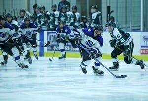 GVL / Emily Frye       Tom Lusynski takes the punk down the ice during the game against Michigan State on Friday Jan. 27, 2017.