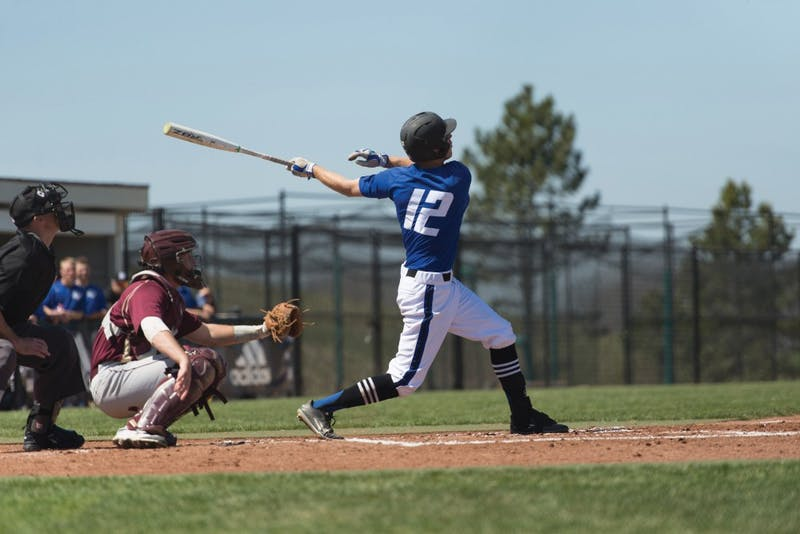GVL / Luke Holmes - Alex Young (12) watches after hitting the ball. Grand Valley Men's Baseball lost to Walsh college 3-4 in the first game but won 15-8 in the second game.