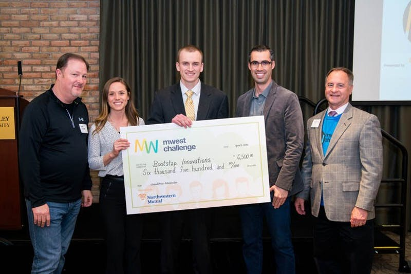 GVL / Courtesy - Bryan Esler Preston Smith and Daniel Diem Rylaarsdam (center) of Bootstrap Innovations win $6,500 during the MWest Challenge, held inside of Grand Valley's Eberhard Center on Friday, April 1, 2016.