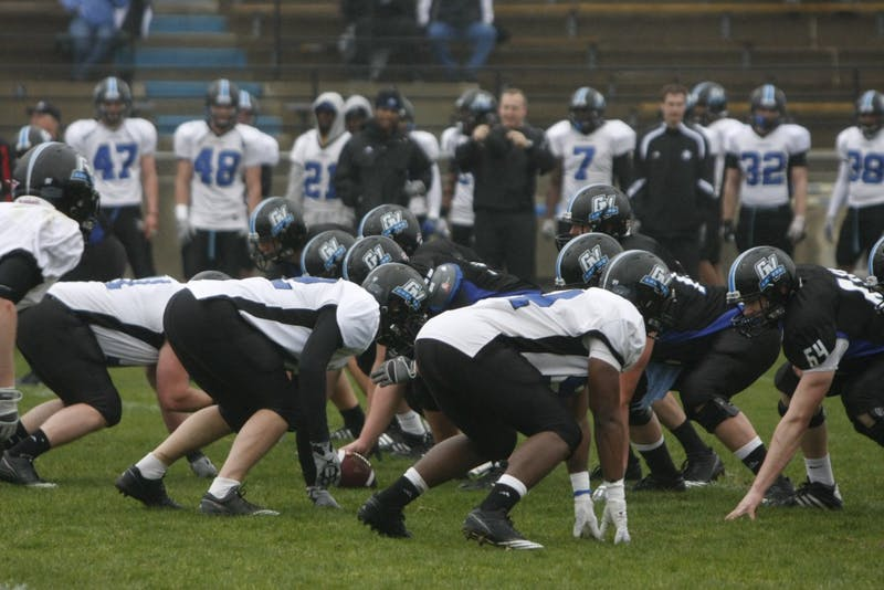 Both the offense and the defense line up before the start of the play during the Sping game on Saturday.