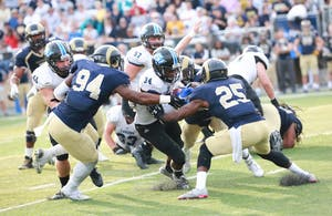 GVL / Kevin Sielaff - Marty Carter (34) is met by Shepherd's Keon Robinson (25) and taken down short of the goal line.  The Lakers fall to the Rams of Shepherd University with a final score of 34-32 Dec. 12 in Shepherdstown, West Virginia.