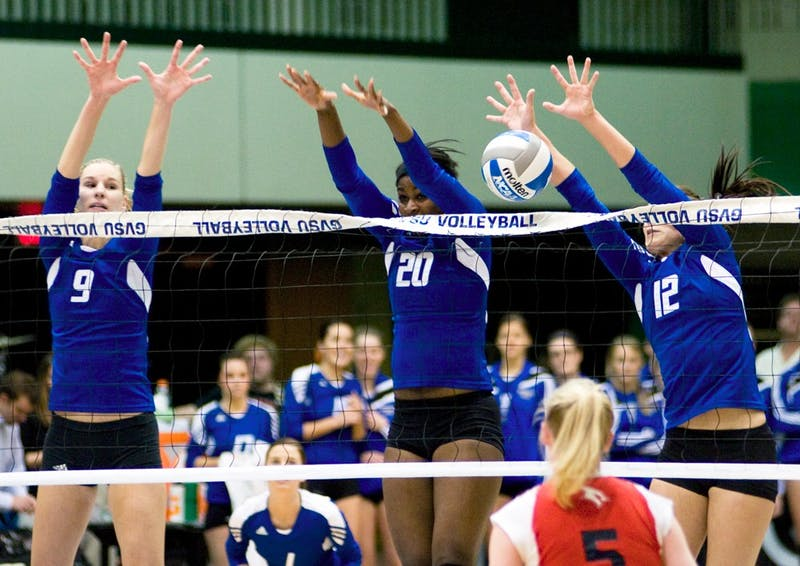 Krysta Kornack, Eno Umoh, and Leslie Curtis spring to the air in attempt to block the ball
