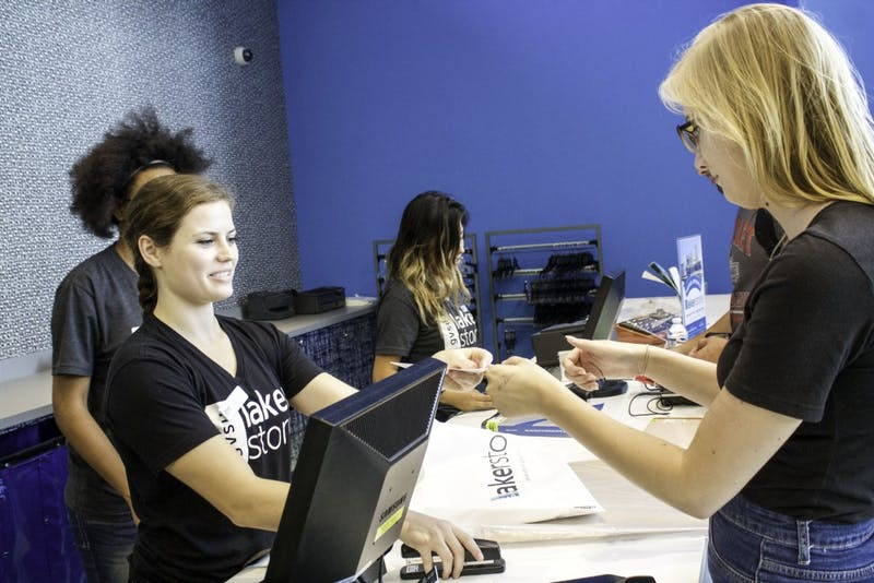 Grand Valley's bookstore employee, Jenn Lee, helps Grand Valley student, Kim Massuch, check out of the new Allendale Bookstore on Tuesday, September 1, 2015.