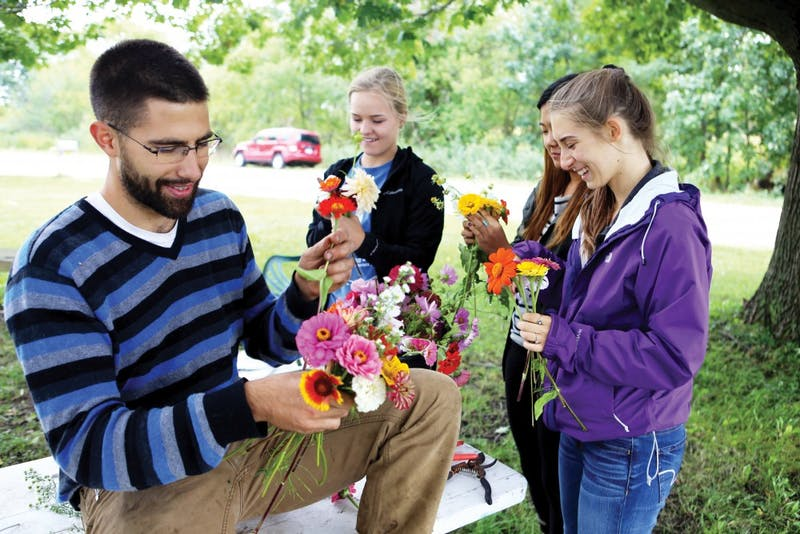 "GVL/Emily Frye - Youssef Darwich (left) gathers bouquets of flowers alongside several Grand Valley student volunteers at the GVSU Sustainability Farm on Friday Sept. 30, 2016. Darwich will be the first to present at ""Climate Change—It's in Our Hands: How Food Choices Impact the Earth"" which will be held Tuesday, Jan. 24, at the L.V. Eberhard Center from 7 p.m. to 9 p.m."