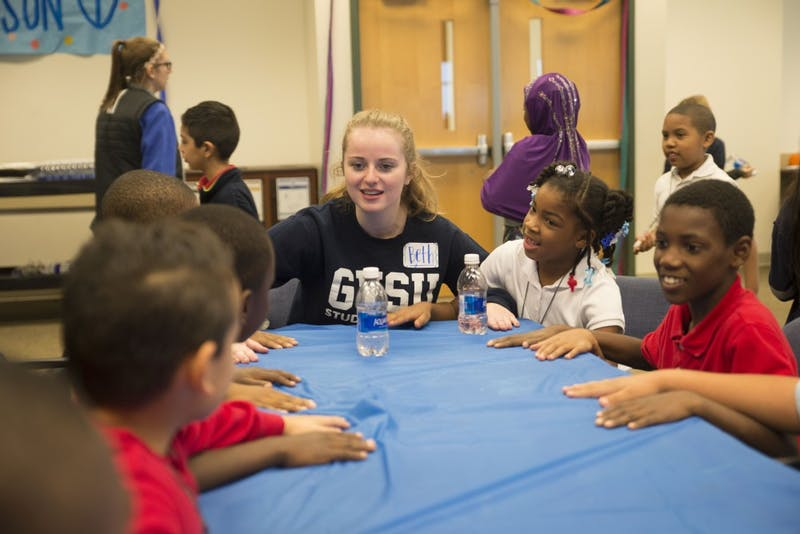 GVL / Luke Holmes - Beth Hopkins plays a game with kids from Dickinson Elementary School.