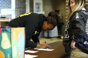 GVL / Kasey Garvelink - Kmystry Taylor-Jackson fills out a sheet saying which cloting items she donated to keep track of inventory at the Greek Closet event on Apr. 12, 2016 in Allendale.