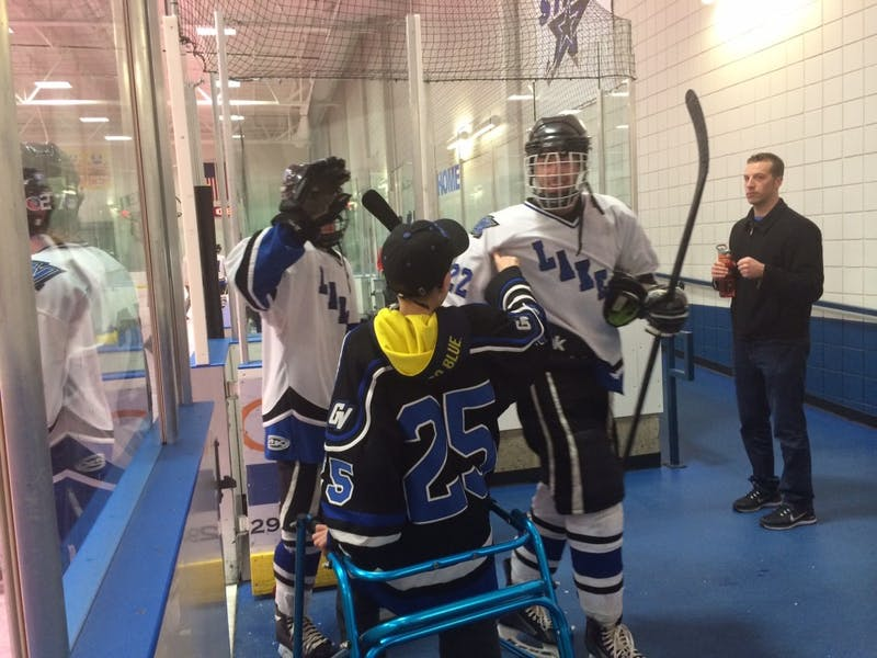 Nathan Vandyken congratulates GVSU hockey players after their win over Davenport.
