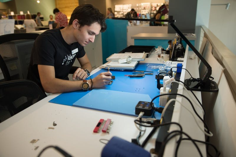 GVL / Luke Holmes - Dylan Kernohan works on a broken iPhone at the Genius Phone Repair shop in the GVSU Marketplace.