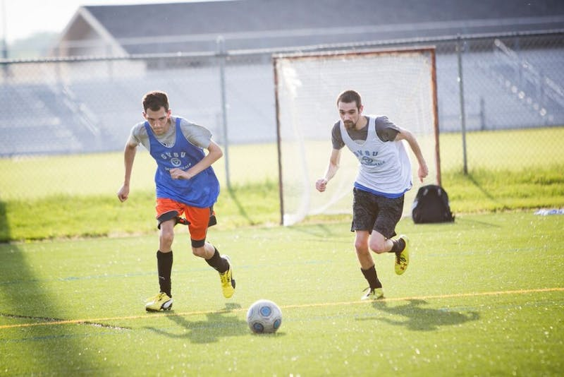 Two members of GVSU's Unified Soccer program race to win a loose ball during a match on Wednesday, June 3. The program will conclude with a championship match on June 10.