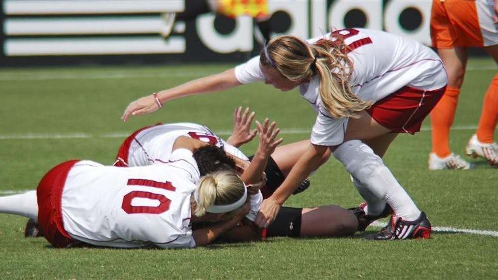 Players lunge onto sophomore midfielder Devon Beach after she headed a goal in the 58th minute of their 2-1 victory against No. 6 Florida on Friday afternoon at Bill Armstrong Stadium. Beach also assisted on the game-winning goal in double overtime. The Hoosiers now hold a perfect 4-0 record.