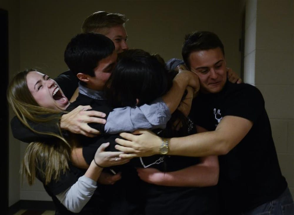 Members of YOUniversity hug after hearing that they won the IUSA election on Wednesday at the Beta Theta Pi House. YOUniversity won the vote by a sizable margin.