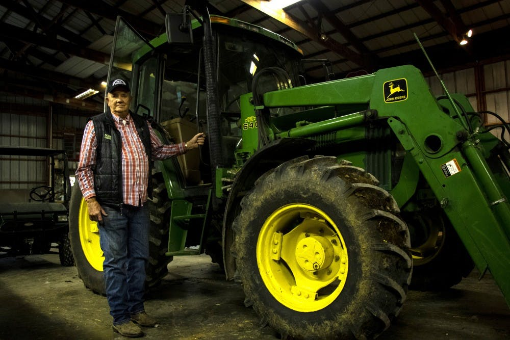 <p>Joe Peden, owner of Peden Farms, stands beside his John Deere tractor at his farm Oct 21. Monroe County farmers experienced a rainy spring this year, which effected their crops.</p>