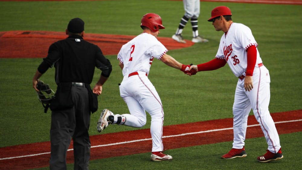 Sophomore Cole Barr rounds third base and shakes hands with Coach Dan Held on April 3 at Bart Kaufman Field. Barr currently has 11 home runs this season.