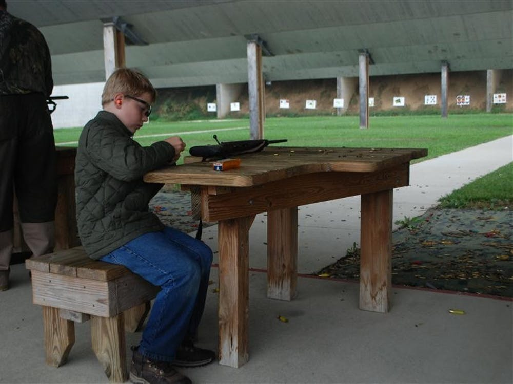 Patrick Ogle loads a gun he is preparing to shoot Sept. 29 at Atterbury Shooting Range. Patrick's father brought him to Hunt, Fish, Eat, which teaches participants how to catch and prepare their own food.