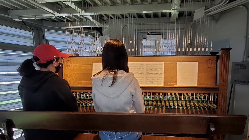 """Graduate student Lynnli Wang plays the carillon with Kyounghwa Oh on Saturday in the Arthur R. Metz Bicentennial Grand Carillon. The """"Meet Me at the Metz"""" recital was dedicated to the Stop Asian Hate movement."""