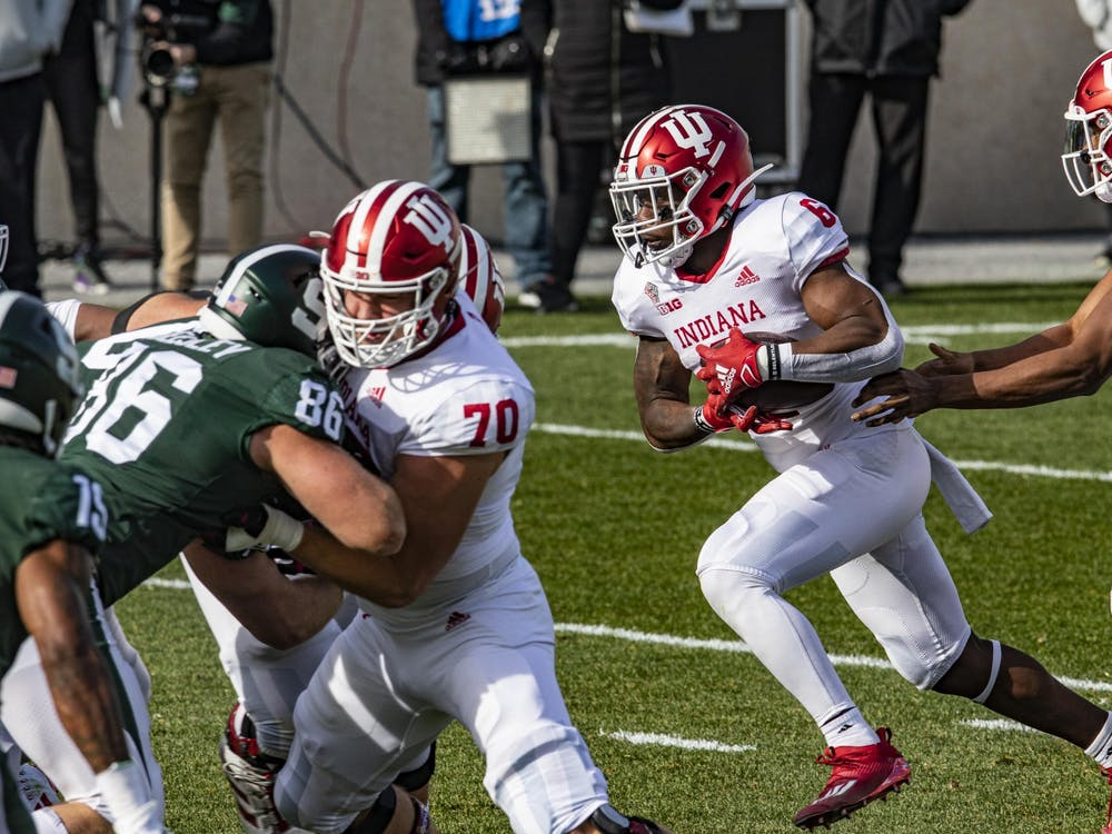 Redshirt sophomore quarterback Michael Penix Jr. passes the ball to sophomore running back Sampson James on Nov. 14, 2020, in Spartan Stadium in East Lansing, Michigan. Penix was named an Anthony Thompson Most Valuable Player on Thursday.