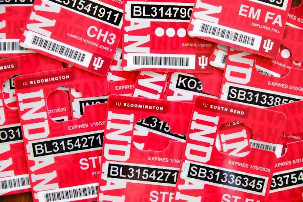 <p>Parking passes lie piled on top of one another. Employees will be able to purchase multiyear parking passes that will not expire until 2024.</p>