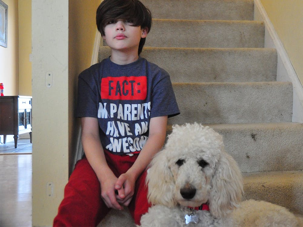 Noah poses with his service dog, Appa.