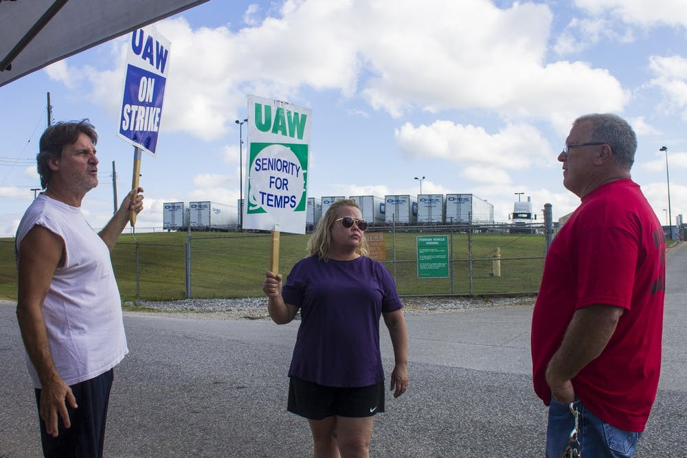 <p>Kevin Hutchinson, who goes by &quot;Hutch,&quot; talks to union strikers in early October outside a General Motors plant in Bedford, Indiana. Ford Motor Company and United Automobile Workers reached a deal this week that will prevent a similar strike at Ford plants.</p>