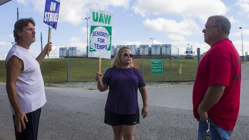"""Kevin Hutchinson, who goes by """"Hutch,"""" talks to union strikers in early October outside a General Motors plant in Bedford, Indiana. Ford Motor Company and United Automobile Workers reached a deal this week that will prevent a similar strike at Ford plants."""