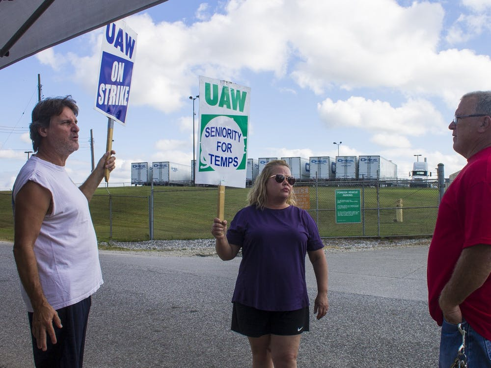 "Kevin Hutchinson, who goes by ""Hutch,"" talks to union strikers in early October outside a General Motors plant in Bedford, Indiana. Ford Motor Company and United Automobile Workers reached a deal this week that will prevent a similar strike at Ford plants."
