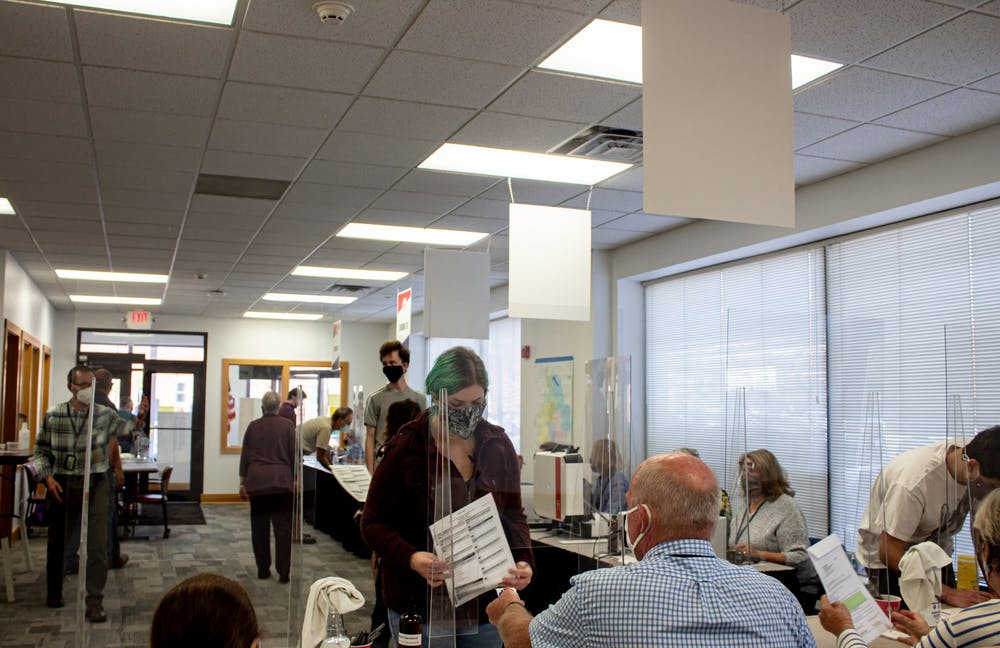 <p>A voter submits their ballot Oct. 6 at 401 W 7th St. Lines have been long most days since early voting began Oct. 6.</p>