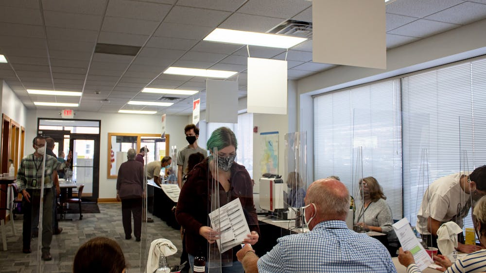 A voter submits their ballot Oct. 6 at 401 W 7th St. Lines have been long most days since early voting began Oct. 6.