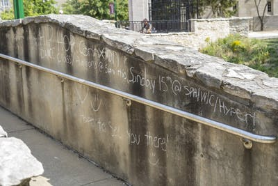 An announcement written in chalk is displayed on a wall Sept. 16 on East Seventh Street. Clubs will often write on sidewalks and walls about call-out meetings in well-trafficked areas.