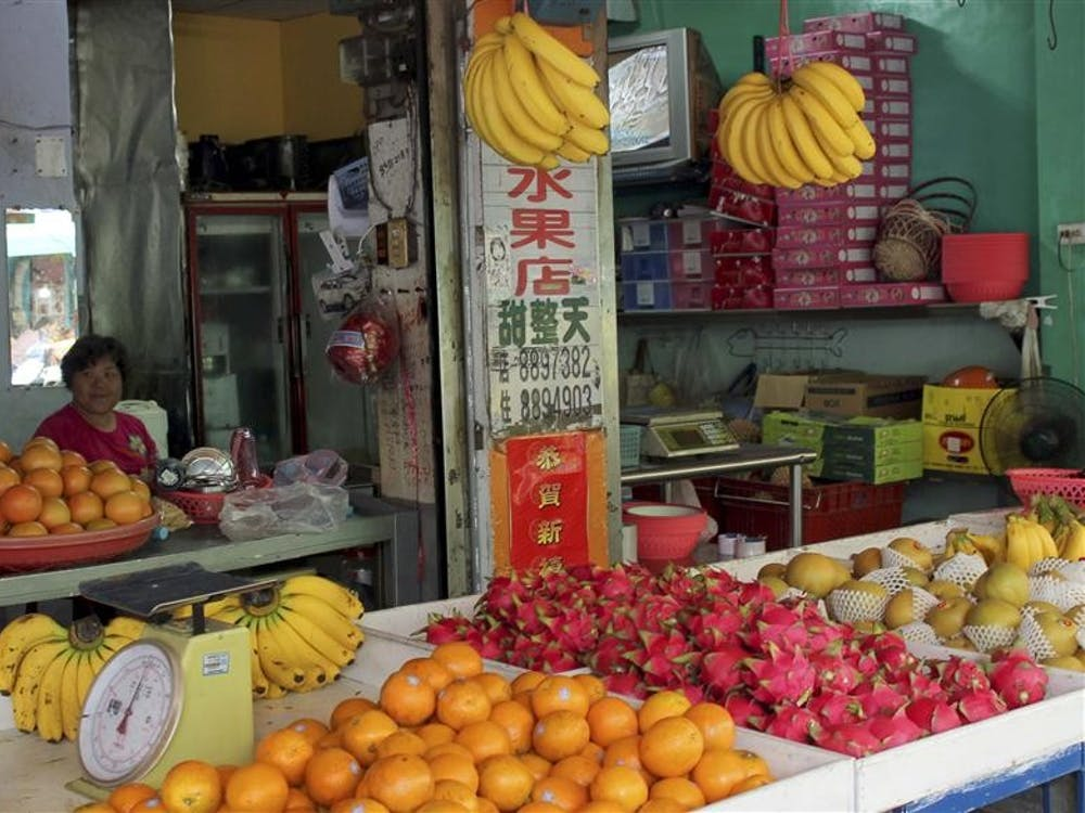 A fruit vendor greets a customer as they approach her fruit stand June 9 at the Hengchun market in Pingtung, Taiwan. Taiwan is known as the kingdom of fruits due to its abundance of exotic fruits such as dragon fruit, durian and mango.