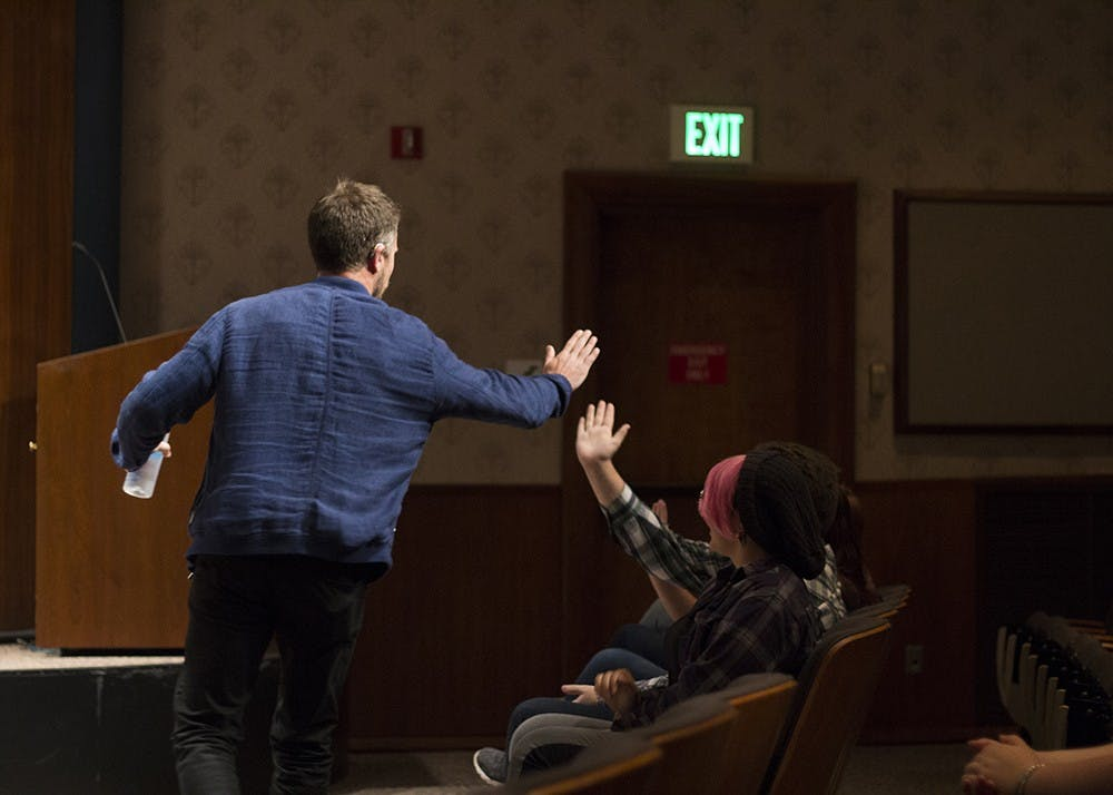<p>D.J. Demers high-fives students as he makes his entrance Tuesday night in the Whittenberger Auditorium. Demers performed his stand-up comedy set at no cost to the listeners. Demers' comedy centers on his observations and experiences while living with and without his hearing aids.</p>