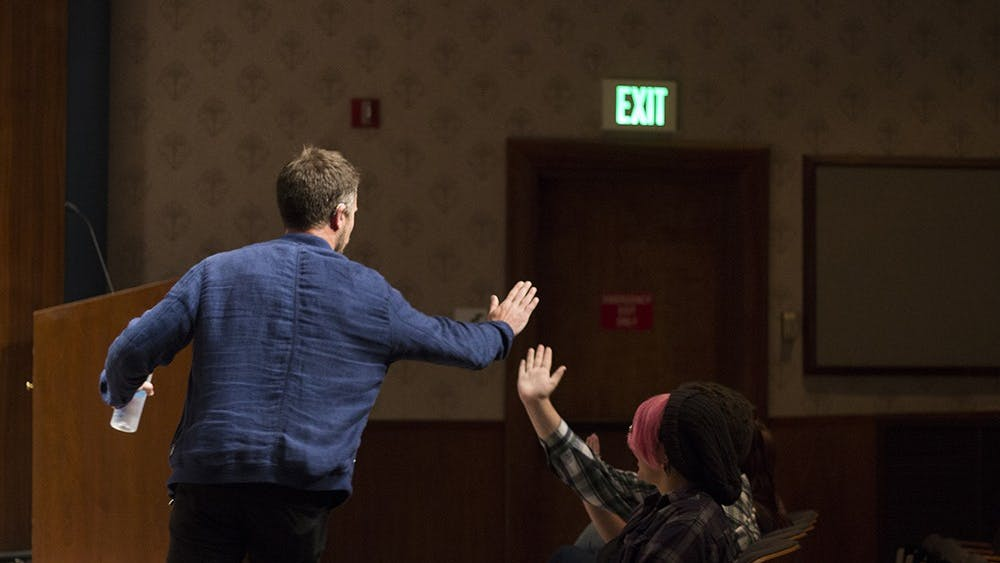 D.J. Demers high-fives students as he makes his entrance Tuesday night in the Whittenberger Auditorium. Demers performed his stand-up comedy set at no cost to the listeners. Demers' comedy centers on his observations and experiences while living with and without his hearing aids.
