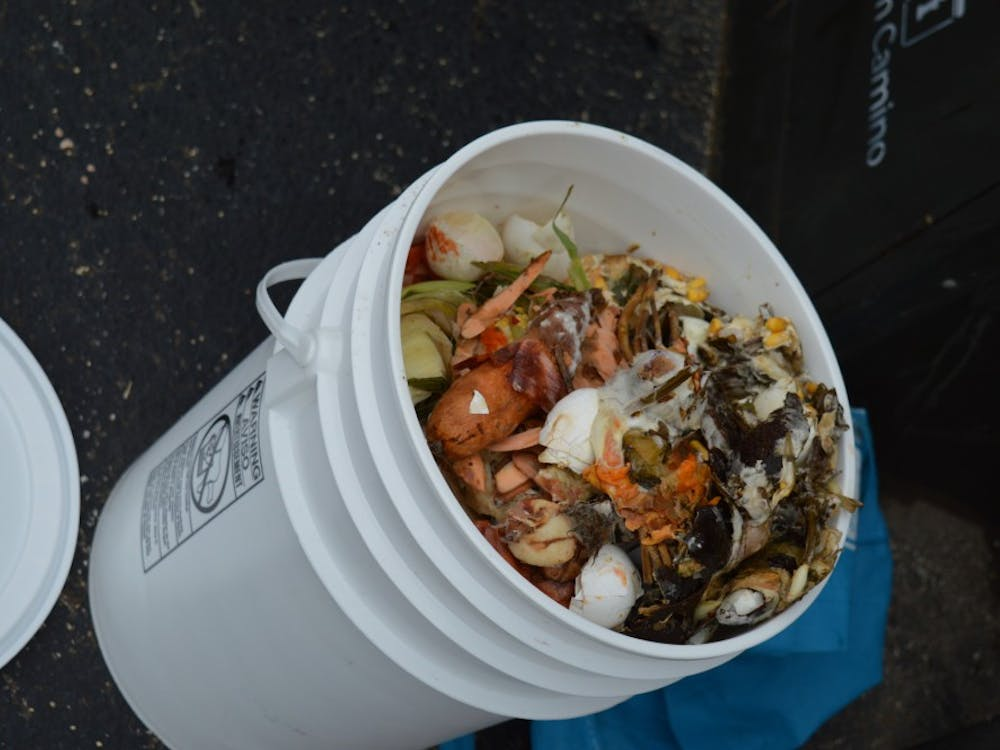 Compost is emptied from pails into a bucket. Green Camino measures the amount of compost each customer contributes.