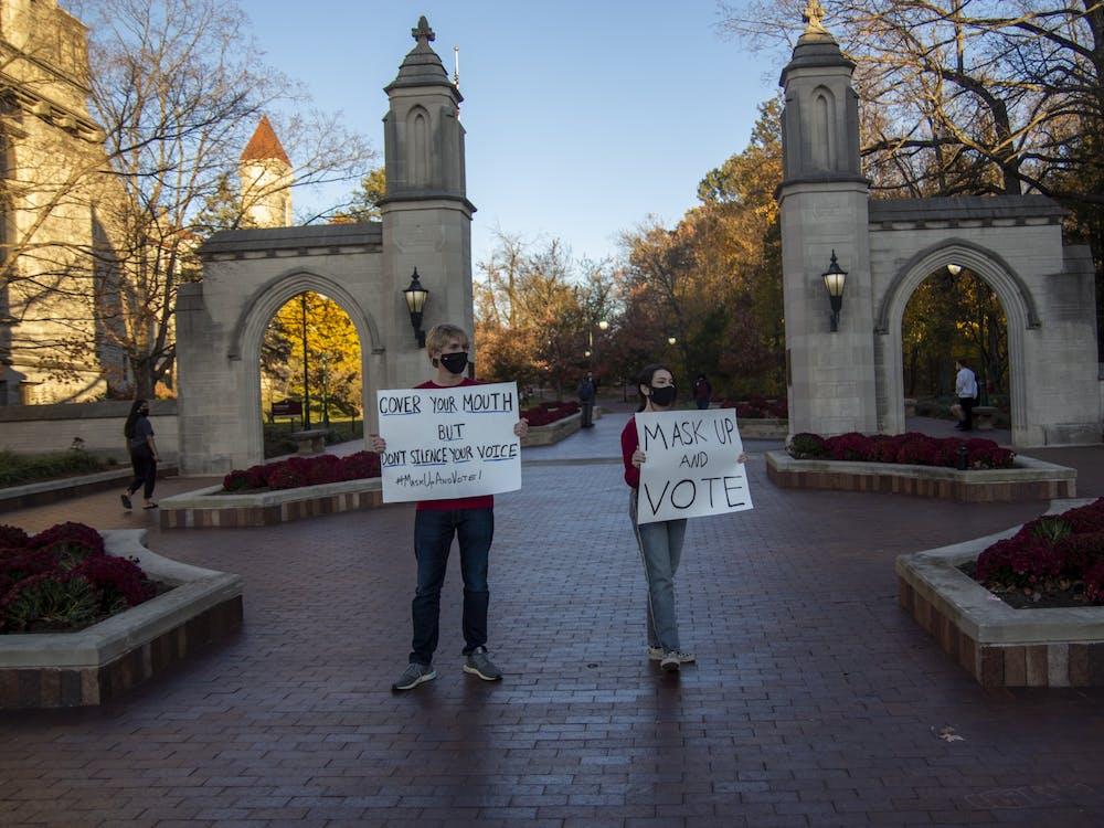 Freshmen Luke Kubehl and Ashley Culbertson hold signs and encourage people to vote Nov. 3 outside the Sample Gates.